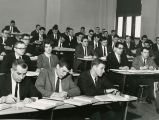 Classroom photo from about 1965-1967 with a single female student among a class of men