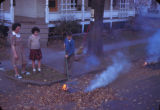 Children burning leaves on street corner