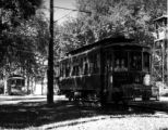 Close up of a trolley car followed by a second trolley car