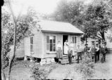Onondaga Nation: People in front yard of small frame house