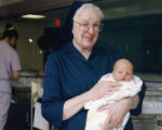 27 Sr. Julia Hermann, DC, holding newborn in nursery at Lourdes Hospital