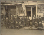 Men in front of Elmira Saddlery Co. [1902]