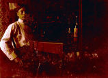 [Young Man in Shirt Sleeves Near a Wine Bottle and Glass]