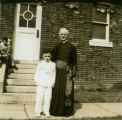 [Priest Standing with a Young Boy]