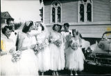 [Bride, groom, bridal party next to church]
