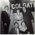 [Three young couples in front of Colgate banner]