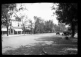 [Unidentified suburban street with houses and businesses (Marshall G. Hay, stationer and...