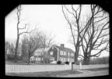 [Unidentified large wood-shake house with white windows and shutters, surrounded by a picket...