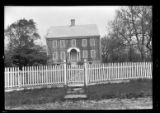 [Unidentified wood-shake house behind picket fence, undated. All shutters closed.]