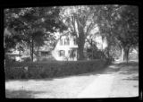 [Unidentified suburban Dutch-style house, undated. Side view over corner hedge.]