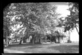 [Unidentified large house with verandah and wisteria vines, partially hidden by trees, undated.]
