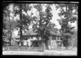 [Unidentified very large house with fence amid tall trees, undated.]