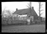 [Unidentified old farmhouse with rickety fence, outbuildings, and additions, undated. Small boy...