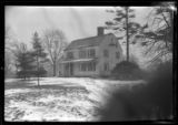 [Unidentified Dutch Revival-style house in winter with snow, undated. Frame partially obscured.]
