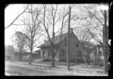 [Unidentified Dutch farmhouse-style house with two additions, in suburban neighborhood, undated.]