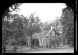 [Unidentified wood-shake house with neat lawn among trees, in the process of being re-shingled,...