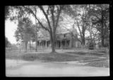 [Unidentified house with wide covered porch and small addition near paved street, undated.]