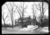 [Unidentified house with wide covered porch and addition near paved street, undated. Winter view...