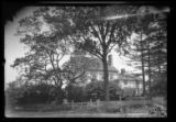 [Unidentified house partly hidden from view by bushes, undated.]