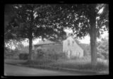 [Unidentified saltbox house behind trees, picket fence, undated.]