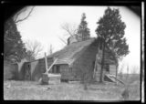 [Unidentified dilapidated wood-shake saltbox house with boarded windows, undated. Rear 3/4 view.]