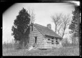 [Unidentified dilapidated wood-shake saltbox house with boarded windows, undated. 3/4 view.]