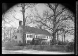 [Unidentified large clapboard house in good repair surrounded by fence and small pines, undated.]