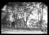 [Unidentified large Cape Cod house on tree-lined street, undated.]