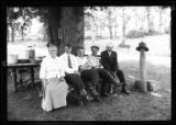 [Five unidentified people posed on a bench under a tree, undated.]