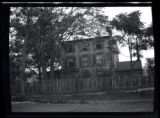 Long Island City: [unidentified 3-story wood-shake house behind a worn picket fence, undated.]
