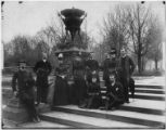 J.S. Hall (James Sheridan Hall) and friends, posed by an ornamental urn in Prospect Park, undated.