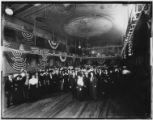 Large group of people in an unidentified ballroom draped in flags and bunting, undated. Includes...