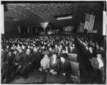 People assembled in an unidentified meeting hall hung with American and Greek flags, undated (ca....