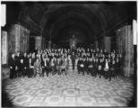 Unidentified group posed in a ornate hall around an unidentified statue, undated.