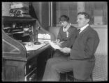Aaron Bers and unidentified woman [secretary?], at a desk in 10 1/2 Debrosses Street, New York...
