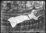 Ethel Magaw Hassler in a hammock, undated (ca. 1905-1910). Double exposure with an item of printed...