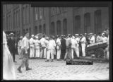 Crowd listening to unidentified man giving a speech on the corner of W. 16th Street and Tenth...