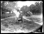Infant William Bjorkman and toddler Virginia Bjorkman pushing a wheelbarrow in a back garden with...