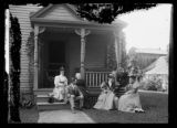 Informal family group seated in front of a house, location unidentified, undated (ca. 1890-1900).