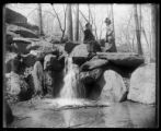 Ginnie and an unidentified woman standing on boulders above a small waterfall, location...