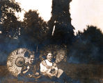 Dorothy (Martin) Foster and friend with Japanese parasols in garden