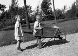 "Margaret pushing brother Darwin M. Foster in ""Graycliff"" wheelbarrow at Graycliff"