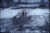 Remediation workers walking on clay capped Love Canal in winter toward Wheatfield Ave.  with...
