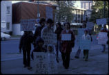 Love Canal protesters, including children, march along street carrying signs