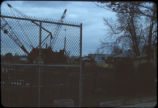 Remediation work at Love Canal showing crane and other heavy equipment behind fence and...