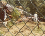 Demolition of abandoned homes at Love Canal seen through a chain-link fence