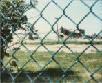 Demolition of 99th Street School seen through chain-link fence