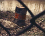 Barrel of toxic waste removed from creek in fenced-in area at Love Canal