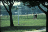 People walking near the fenced-in containment zone at Love Canal