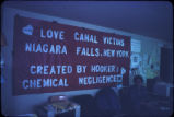 Debbie Cerrillo in the Love Canal Homeowners Association offices with Love Canal victims banner:...